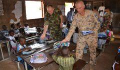 Deux militaires (irlandais et estonien) remettent des kits scolaires ( Crédits: EUTM Mali)