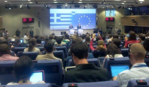 La salle de presse pavoisée des drapeaux grec et européen, pleine à craquer (© NGV / B2)
